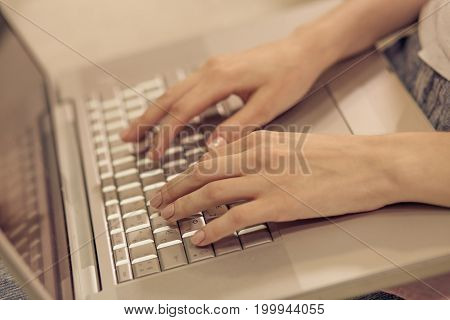 Close up view of woman hands keyboarding on laptop. Female working with computer, typing.