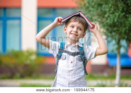 Child With Book On His Head Outdoors