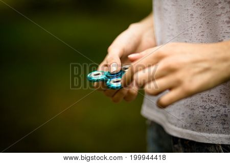 Young girl playing with fidget spinner outdoors. View of woman hand holding modern spinner toy in her hands.