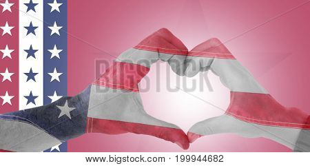 Couple making heart shape with hands against close-up of an flag