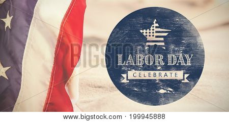 Digital composite image of celebrate labor day text with American flag on blue poster against close-up of sand surface