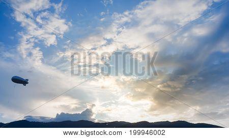 Helium blimp advertising ballon floating sunset sky and mountain background poster