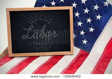 Composite image of happy labor day and god bless America text against blank chalkboard on american flag