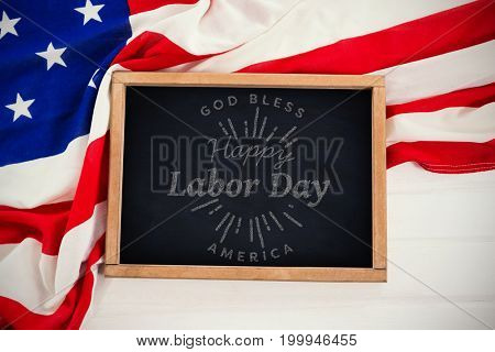 Digital composite image of happy labor day and god bless America text against chalkboard on american flag