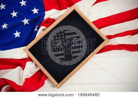Cropped hand holding tool and american flag on red poster against high angle view of chalkboard with american flag