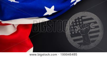 Cropped hand holding tool and american flag on red poster against american flag on empty slate