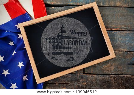 Digital composite image of happy labor day text on blue poster against american flag with chalkboard on table