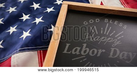 Digital composite image of happy labor day and god bless America text against american flag and slate on wooden table