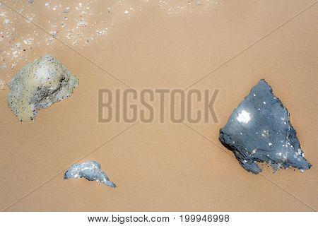 Black rock heart shape on sand glow effect