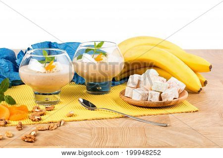 A composition of two dessert glasses filled with thick beverages isolated on a white background. Banana smoothie with decorative mint leaves, physalis and a metal spoon on a light wooden table.