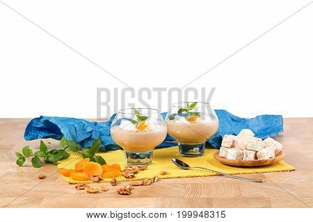 A beautiful composition of two dessert glasses filled with thick cocktail isolated on a white background. Smoothie with decorative mint leaves, rahat lukum, and dried apricots on a light wooden table.