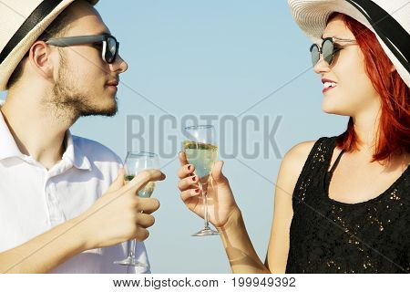 Beautiful couple of lovers sailing on a boat. Two fashion models posing on a sailing boat at sunset
