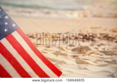 Blurry animated flare against starfish with sea shells and a bottle of sunscreen lotion on sand