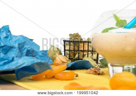 A close-up picture of dessert glass filled with thick banana dessert isolated on a white background. Tropical smoothie with decorative mint leaves, physalis and dried apricots on a bright yellow cloth.
