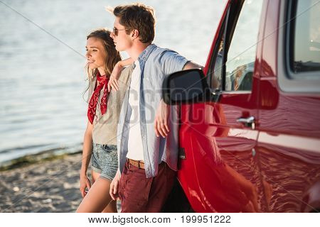 Young Couple With Car At Riverside