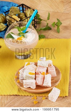 A colorful light set of classic turkish delight, thick banana cocktail in a big glass and tropical physalis fruits on a decorative yellow fabric on a wooden desk background. Nutritious healthy snacks.