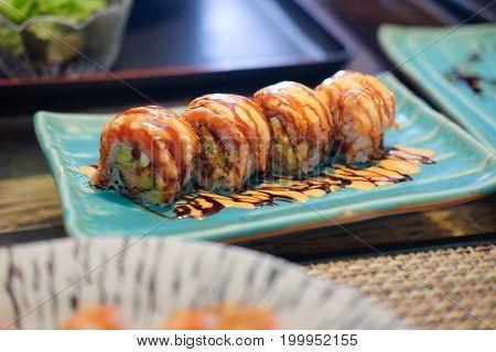 Salmon sushi rolls on blue plate, Japan food