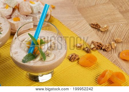 A table with a plate of lokum, Turkish delight, a glass of grated walnuts, dried apricots and slices of bananas, adorned with leaves of mint on a blurred colorful background.