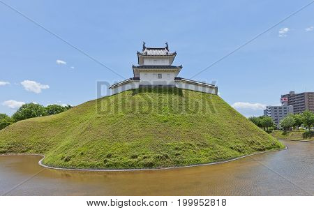 UTSUNOMIYA JAPAN - JUNE 2 2017: Reconstructed moat earthen wall and Seimeidai Turret of Utsunomiya Castle Japan. Castle was founded in 1062 destroyed in war of 1868 and reconstructed in 2007