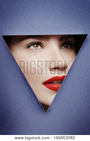 Young woman face looking thru blue or turquoise torn cardboard as beauty concept with copyspace