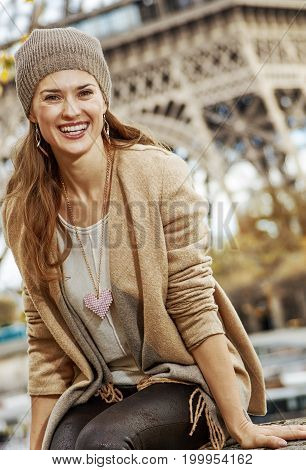 Tourist Woman Sitting On Parapet On Embankment Near Eiffel Tower