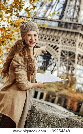 Tourist Woman On Embankment In Paris Holding Map And Pointing