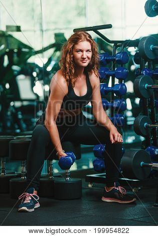 Feel that burn! A fit sporty young woman is sitting in profile on a bench in profile lifting weights with one hand while resting her elbow on her knee.