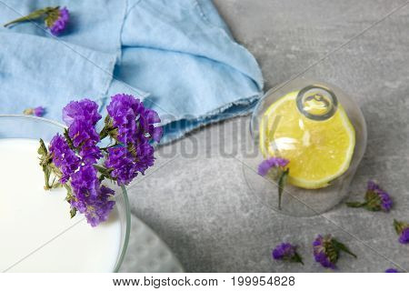 A top view of a table with blue napkins, vivid sappy yellow lemon, a glass of fresh milk and a twig of little flowers, table setting for supper or dinner on a light gray background close-up.