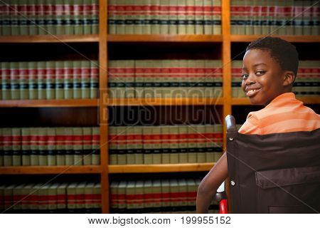 Portrait of cute boy sitting in wheelchair against volumes of books on bookshelf in library