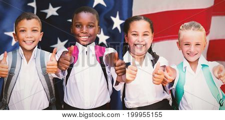 Portrait of students showing thumbs up sign against flag with stripes and stars