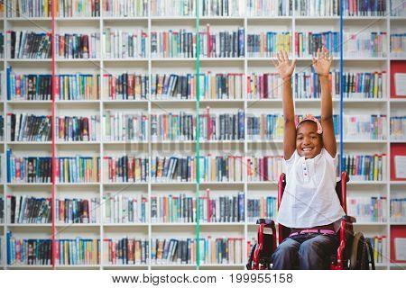 Girl in wheelchair in school corridor against multi colored bookshelf in library