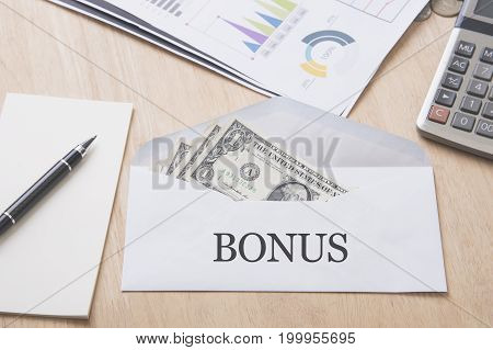 dollar money in the envelope on wood table. bonus reward benefits concept.