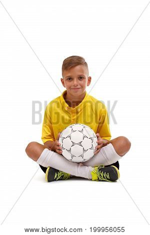 A young footballer sitting on a floor and holds a ball in hands, a young boy in a sports uniform isolated on a white background, concept, rivalry, football, soccer, competition, match.