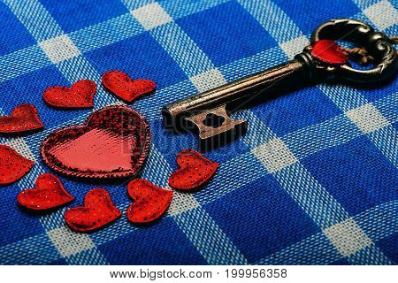 metallic key and small sweet red hearts symbol of love for valentines day holiday celebration on white and blue plaid fabric or checkered cloth background side view