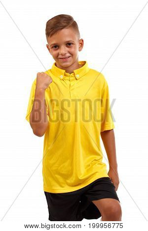 A smiling schooler with a raised fist. Delighted little kid isolated on a white background. A little boy in a bright yellow T-shirt and black shorts. Sports, championship concept.