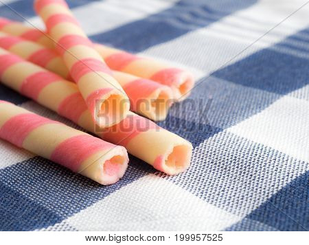 pink striped wafer rolls on blue plaid tablecloth.