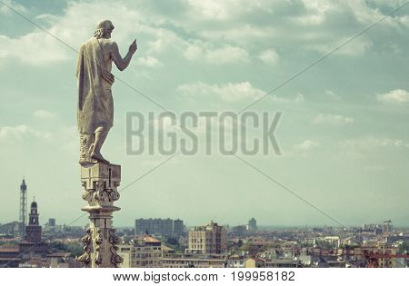 Marble statue on the stone spire of the roof of the Milan Cathedral overlooking Milan, italy. Milan Duomo is the largest church in Italy and the fifth largest in the world.