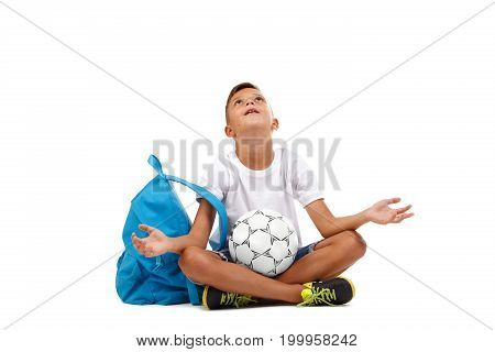 A sportive kid isolated on a white background. A little young man with a ball and a blue satchel sitting on the ground in a lotus pose and praying for victory. Sports, championship concept.