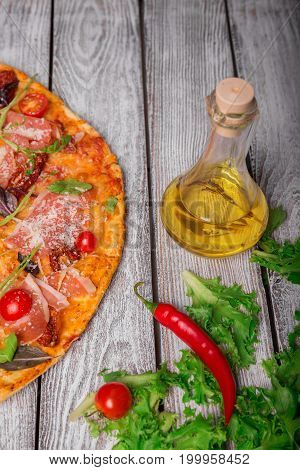 A close-up picture of a tasty pepperoni pizza with a glass bottle of olive oil and salad leaves. Hot bright dish on a rustic wooden table background. Cooking concept. Italian cuisine.
