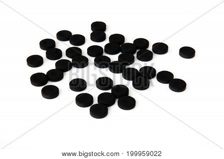 Activated charcoal pills isolated on white back