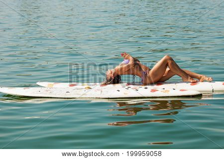 adult fitness woman in bikini exercise on windsurf board on  water of river, lake or sea
