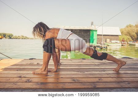 woman fitness instructor exercise outdoor on wooden river raft summer day