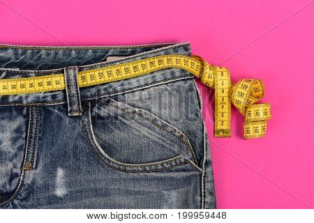 Upper part of denim trousers isolated on pink background. Healthy lifestyle and dieting concept. Blue jeans with yellow measure tape instead of belt. Close up jeans with measure tape around waist.