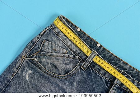 Close up of jeans belt loops and pocket. Top part of denim trousers isolated on blue background. Jeans with yellow measure tape instead of belt. Healthy lifestyle and dieting concept.
