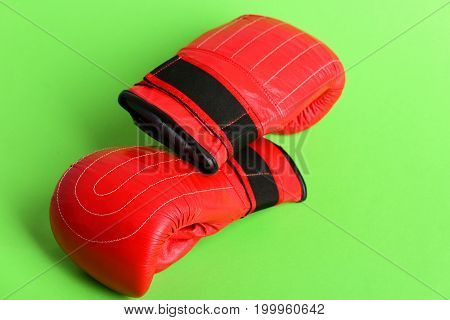 Pair Of Red And Black Boxing Sports Gloves On Green