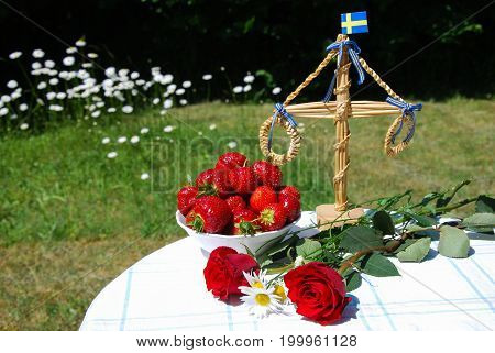 Table in a garden ready for swedish midsummer celebration