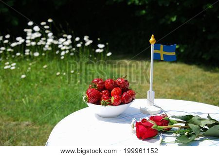 Table set for summer event in a garden with strawberries flowers and a swedish flag