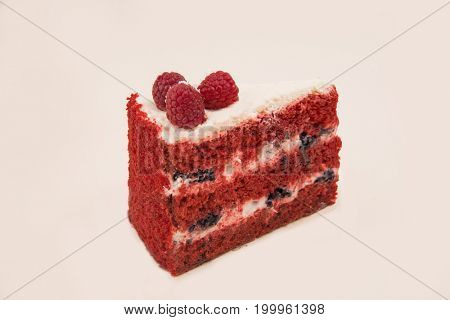 Side view of red pie with raspberries and white cream isolated over white