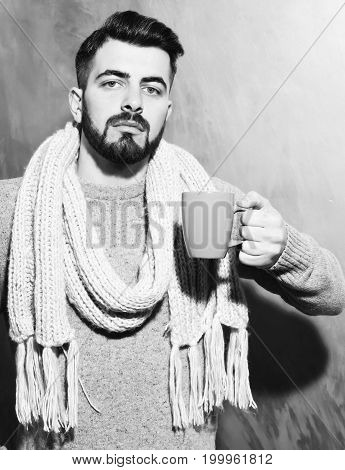 bearded man long beard brutal caucasian hipster with moustache dressed in sweater and scarf holding blue cup of tea or coffee with serious face on brown studio wall background