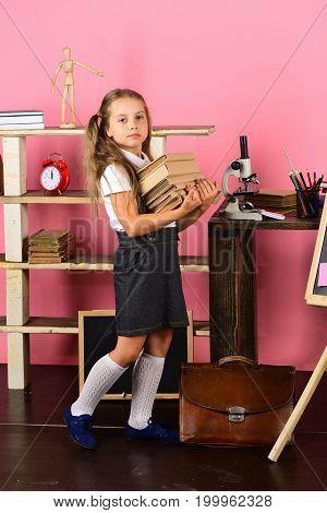 Girl With Ponytails Stands By Bookshelf And Big Schoolbag